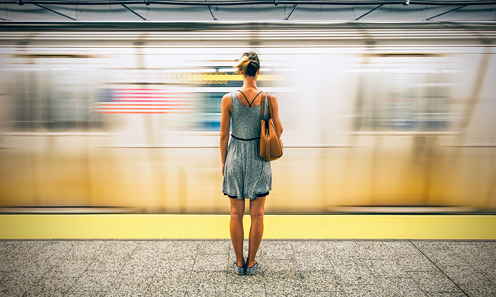 Girl standing in front of blurry moving subway in New York