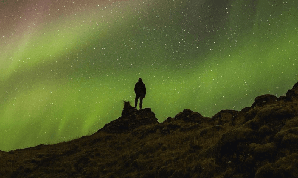 Silhouette of a person standing atop a mountain in front of the Northern Lights